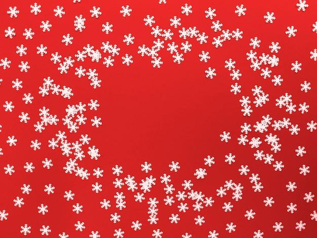 Verspreide witte sneeuwvlokken op rode achtergrond. eenvoudig plat leggen met kopie ruimte. Premium Foto