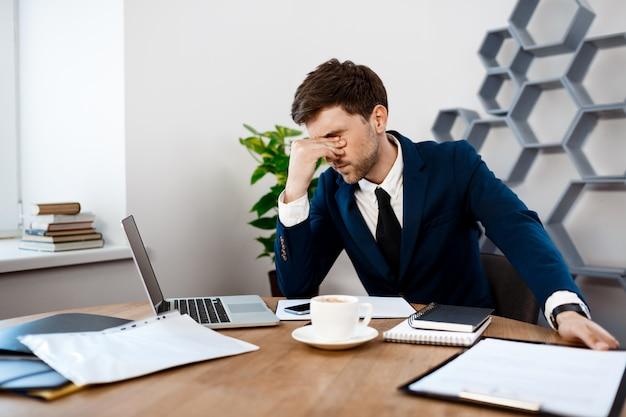Verstoor jonge zakenmanzitting op werkplaats, bureauachtergrond. Gratis Foto
