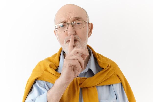 Vertel het aan niemand. menselijke gezichtsuitdrukkingen en lichaamstaal. ernstige oudere ongeschoren kale man gekleed in elegante kleding houdt de vinger naar zijn mond, zegt shh en vraagt om zijn geheim Gratis Foto