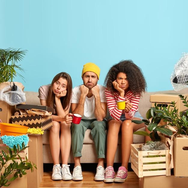 Verticaal beeld van ontevreden drie multi-etnische vrienden verhuizen naar een andere plaats, hebben koffiepauze na het uitpakken van spullen, kijk met ontevredenheid, zitten op de bank tegen blauwe muur in de woonkamer Gratis Foto