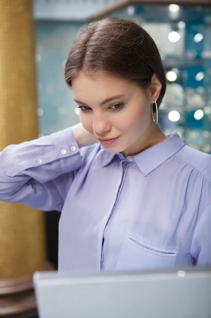 Verticaal portret van een mooie vrouw die hoepeloorringen bij juwelierswinkel probeert Premium Foto