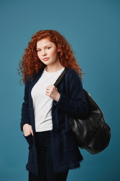 Verticaal portret van knappe vrouwelijke student met golvend rood haar, die hand in zak houdt, die zwarte zak houdt, die gelukkige en zekere blik heeft. Gratis Foto