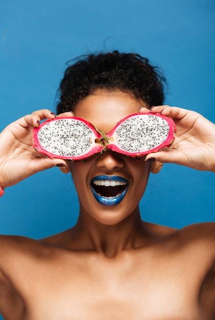 Verticaal portret van vrolijke afrikaanse amerikaanse vrouw die rond voor de gek houden terwijl het behandelen van ogen met exotische pitahayafruit die in half geïsoleerd, over blauw wordt gesneden Gratis Foto