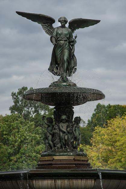Verticaal schot van bethesda-fontein in de stad van new york, de vs met een sombere hemel op de achtergrond Gratis Foto