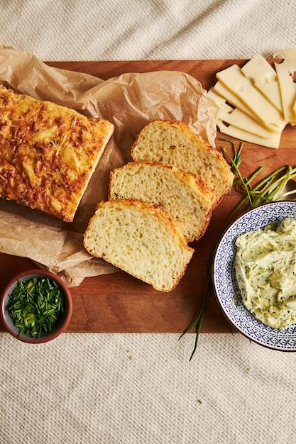 Verticaal schot van brood met kaas, kruidenboter op een hout Gratis Foto
