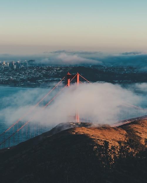 Verticaal schot van de golden gate bridge achter de wolken met gebouwen in de verte Gratis Foto