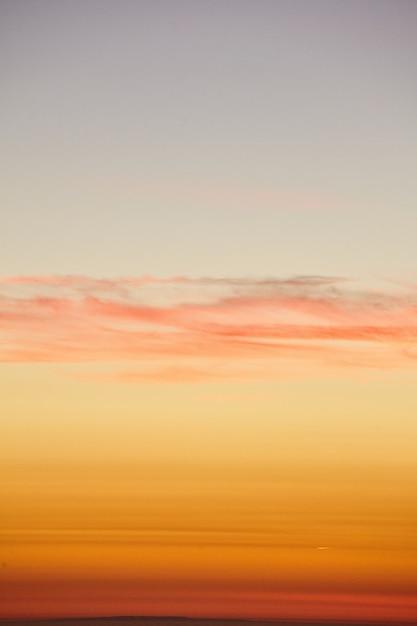 Verticaal schot van de gouden zonsonderganghemel over de stille oceaan Gratis Foto