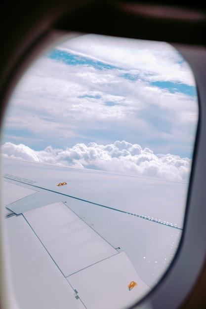 Verticaal schot van de wolken die uit een vliegtuigvenster worden gevangen Gratis Foto