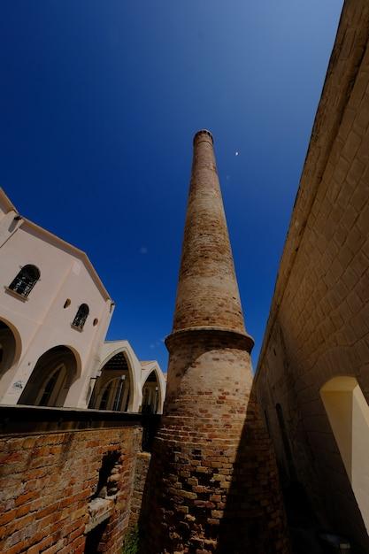 Verticaal schot van een baksteentoren dichtbij een vermelding op een zonnige dag Gratis Foto
