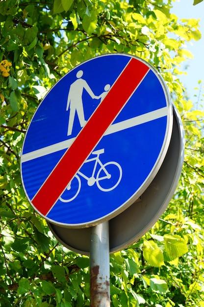 Verticaal schot van een blauw bord dat de toegang van mensen en fietsen verbiedt Gratis Foto