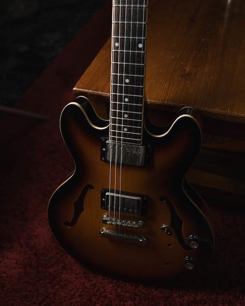 Verticaal schot van een bruine akoestische gitaar op de grond Gratis Foto