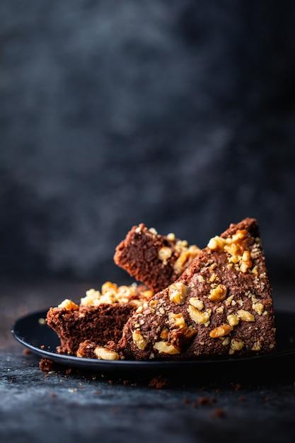 Verticaal schot van een chocoladecake met okkernoten in een zwarte plaat met vaag Gratis Foto