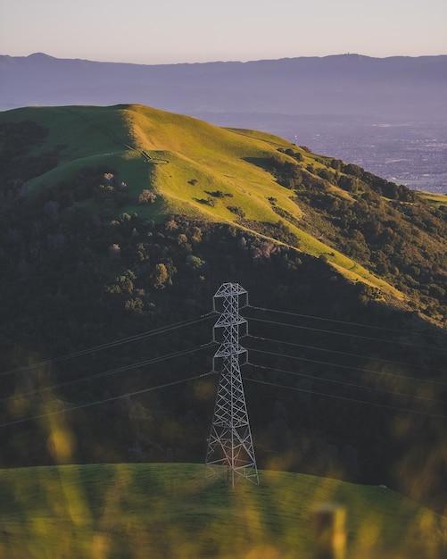 Verticaal schot van een elektrische toren op een met gras begroeide berg Gratis Foto