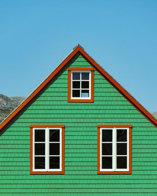 Verticaal schot van een houten groen huis onder de duidelijke blauwe hemel Gratis Foto