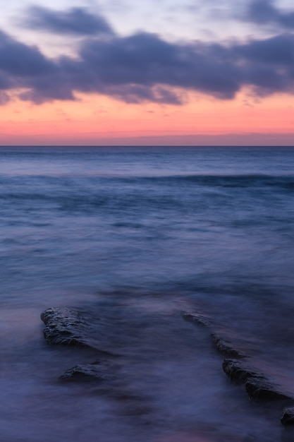Verticaal schot van een kalme oceaan met kleine golven en een oranje bewolkte hemel Gratis Foto