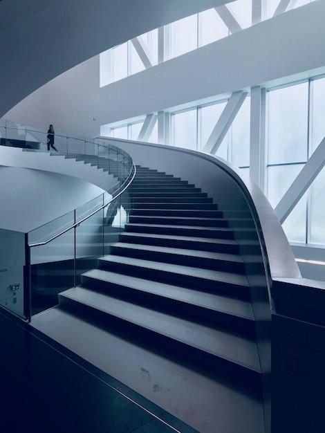 Verticaal schot van een moderne trap in een mooi wit gebouw Gratis Foto