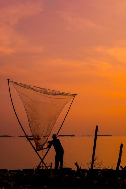 Verticaal schot van een mooie zonsondergang over een overzees met een visser die een net houdt Gratis Foto