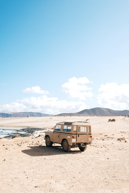 Verticaal schot van een off-road auto die zich in een woestijn bevindt Gratis Foto
