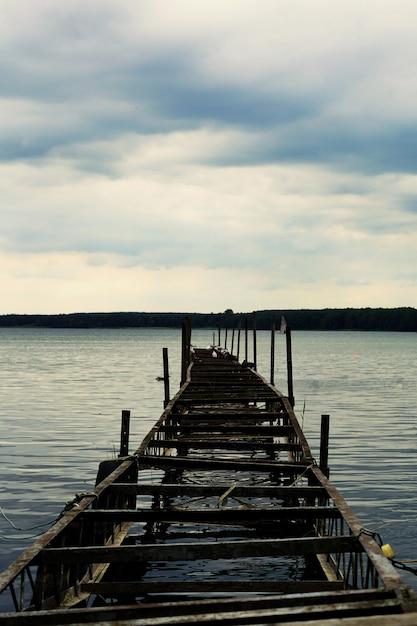 Verticaal schot van een oude half-gebroken pier met bewolkte luchten in miedwie, stargard, polen. Gratis Foto