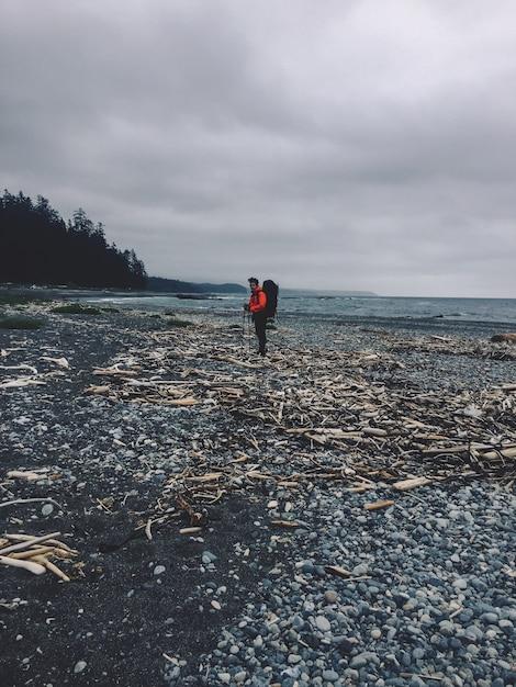 Verticaal schot van een persoon die zich op een rotsachtig strand naast de oceaan bevindt Gratis Foto