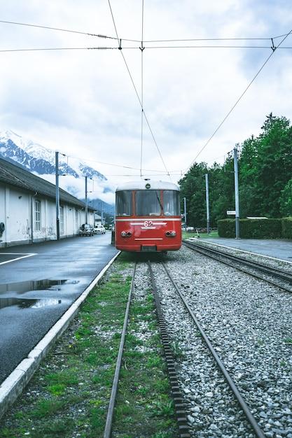 Verticaal schot van een rode tram die zich vooruit door de rails beweegt Gratis Foto