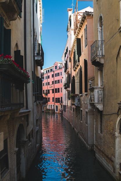 Verticaal schot van een smal kanaal in het midden van gebouwen in venetië italië Gratis Foto