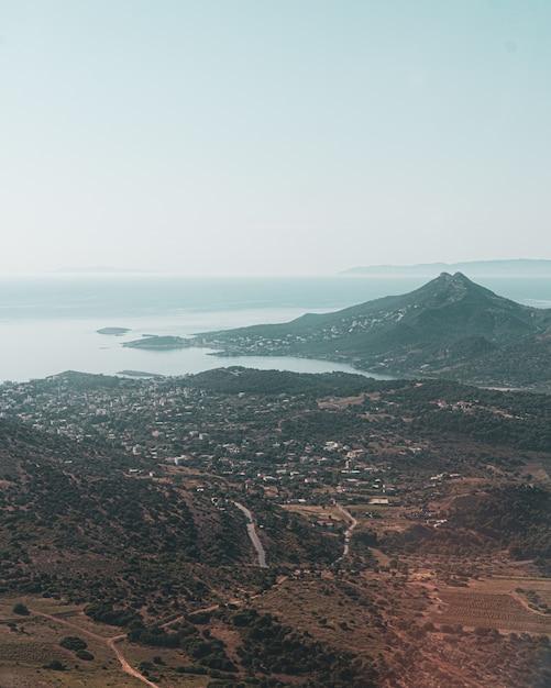 Verticaal schot van een stad en een berg dichtbij de kust in één van de griekse eilanden Gratis Foto