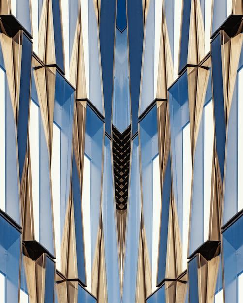 Verticaal schot van een symmetrisch blauw glas en een betonnen gebouw Gratis Foto