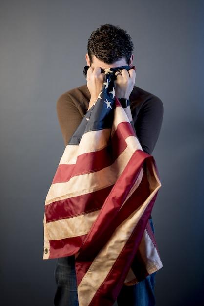 Verticaal schot van een teruggetrokken militair die in verdriet schreeuwt en zijn tranen met de vlag van verenigde staten schoonmaakt Gratis Foto