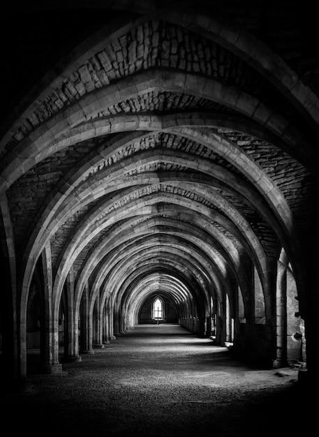 Verticaal schot van gang in zwart-wit bij de crypte bij fountains abbey. Gratis Foto
