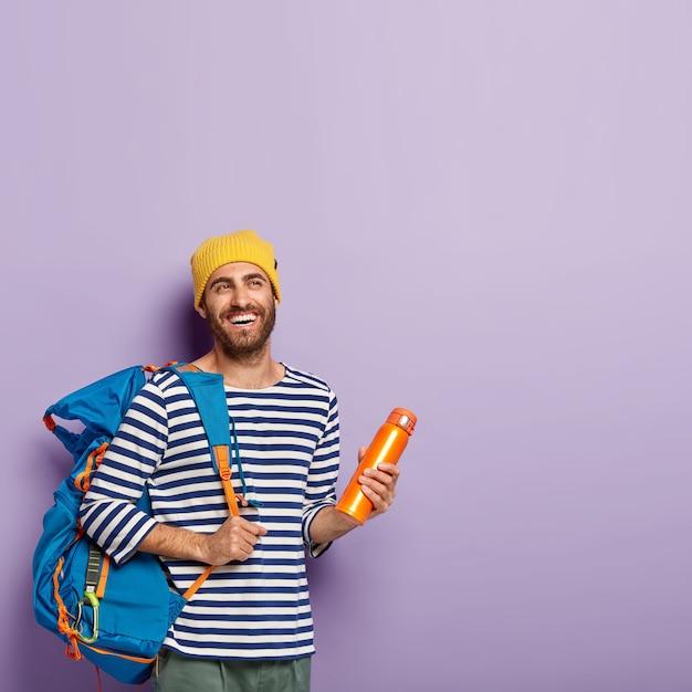 Verticaal schot van gelukkige ongeschoren mannelijke backpacker draagt grote toeristenrugzak, houdt kolf, geïsoleerd over violette muur, vrije ruimte. mensen en toerisme Gratis Foto