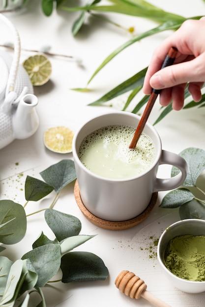 Verticaal schot van groene thee latte met melk in een witte kop met groene bladeren en houten lepel Gratis Foto