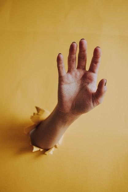 Verticaal schot van iemands handpalm die door een gele document muur breekt Gratis Foto