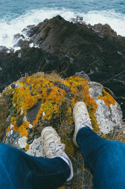 Verticaal schot van iemands voeten die bovenop een klif staan die met mos wordt bedekt Gratis Foto