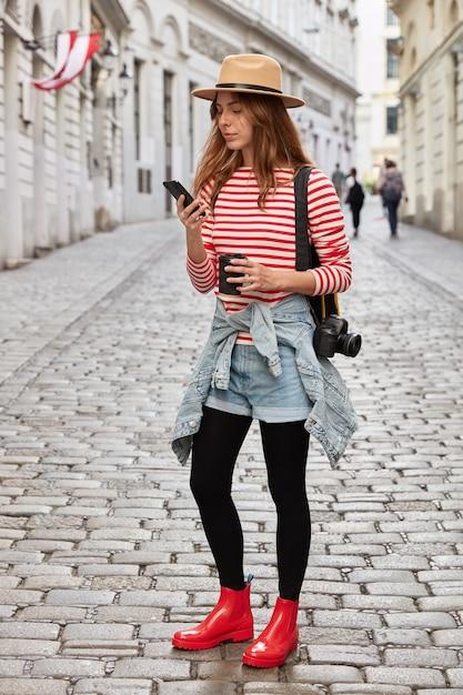 Verticaal schot van modieuze vrouw draagt hoed, gestreepte trui, korte spijkerbroek en rode rubberen laarzen, cellulaire Gratis Foto
