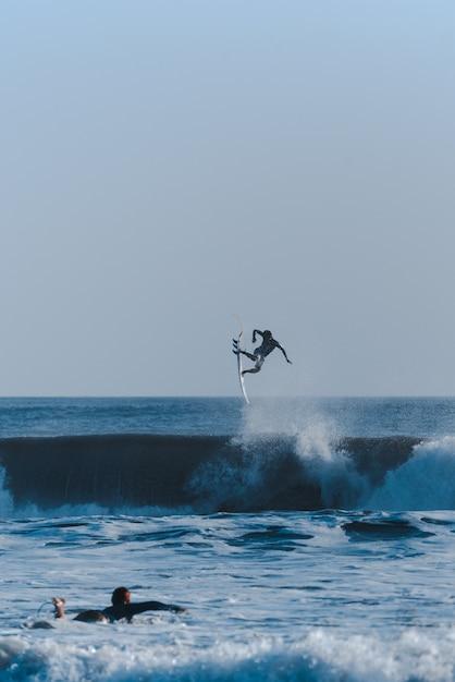 Verticaal schot van surfers die trucs doen in de oceaan die de golven overnemen Gratis Foto