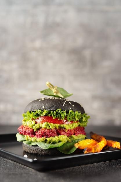 Verticaal schot van veganist zwarte hamburger met gebakken zoete aardappel Premium Foto