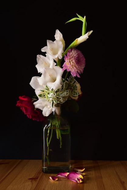 Verticaal schot van verschillende bloemen in een pot op een houten oppervlak met een zwarte achtergrond Gratis Foto