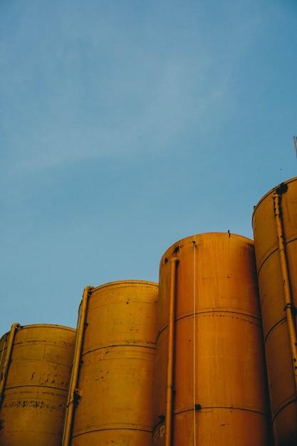 Verticaal schot van vier gele metaalsilo's met de blauwe hemel Gratis Foto