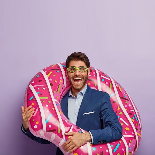 Verticaal schot van vrolijke jonge man met borstelharen, draagt een bril en elegante kleding Gratis Foto