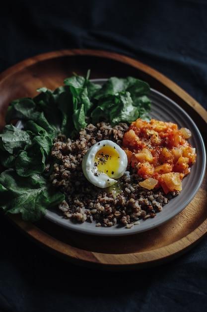 Verticaal selectief schot van een gesneden ei, een boekweit en groenten op een plaat Gratis Foto