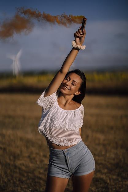 Verticaal shot van een blanke vrouw poseren met rookbom op afstand van velden en windmolens Gratis Foto