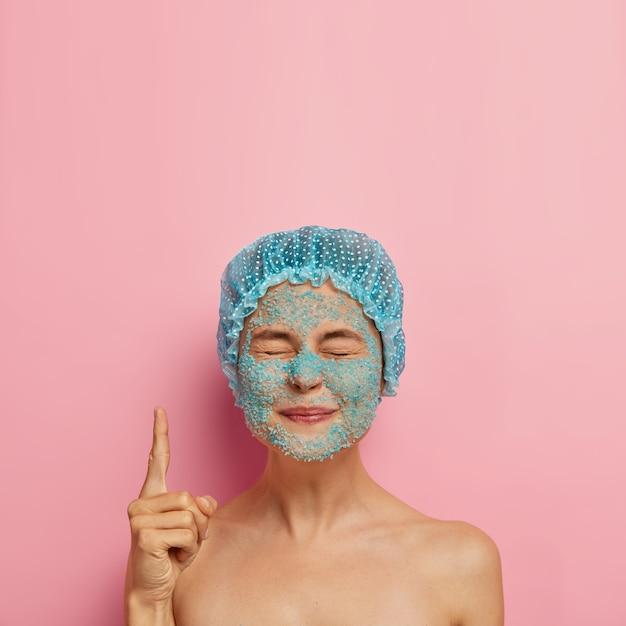 Verticale afbeelding van tevreden schoonheid meisje heeft blauwe zeezout scrub op gezicht, sluit de ogen en wijst wijsvinger naar boven, draagt een badmuts, brengt weekend door in spa salon heeft problematische droge huid, schoonheidsregime Gratis Foto