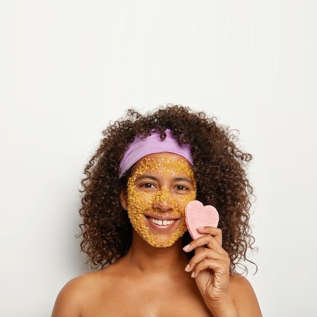 Verticale afbeelding van vrolijke, gelukkige vrouw past zeezout scrub toe voor het absorberen van vuil en het reinigen van donkere stippen op het gezicht, zorgt voor een goede hydratatie, houdt een hartvormige spons bij de wang, keert huidcellen om Gratis Foto