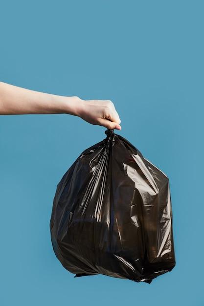 Verticale afbeelding van vrouwelijke hand met zwarte vuilniszak, afval sorteren en recycling concept Premium Foto