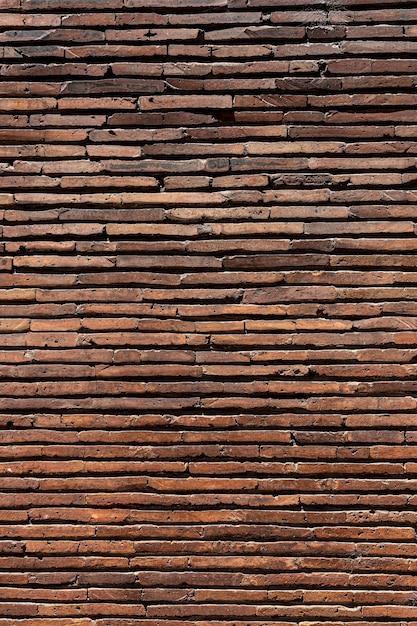 Verticale bruine bakstenen muur achtergrond Gratis Foto