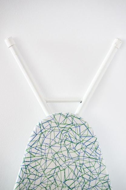 Verticale close-up die van een strijkplank is ontsproten die op een witte muur wordt geleund Gratis Foto