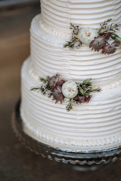 Verticale close-up shot van een drielaags bruidstaart versierd met bloemen op een zilveren schotel Gratis Foto