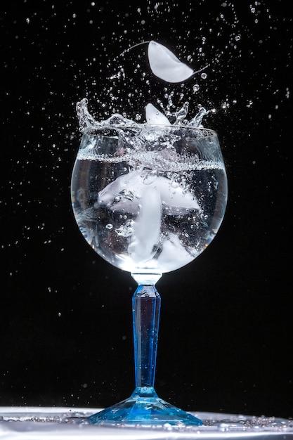 Verticale close-up shot van een glas ijskoud water met spatten Gratis Foto