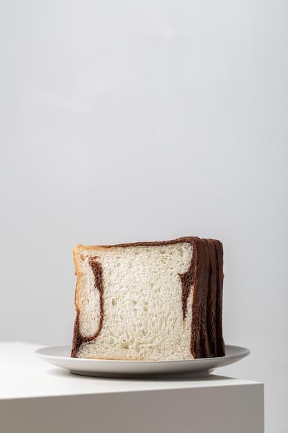 Verticale close-up van witte broodplakken gemengd met chocolade op een plaat op de tafel onder de lichten Gratis Foto